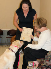 Laura presenting certified therapy dog with certificate.